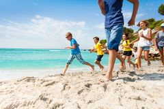 Grupp av lyckliga ungar som kör på den vita sandstranden Arkivbild