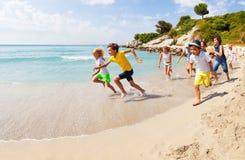 Grupp av lyckliga ungar som springer på den sandiga stranden Arkivbild