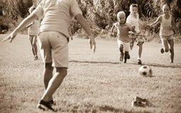 Grupp av lyckliga ungar som tillsammans spelar fotboll på grön gräsmatta i p royaltyfri fotografi