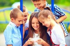 Grupp av lyckliga ungar som tillsammans spelar online spel, utomhus Arkivbilder