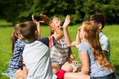 Grupp av lyckliga ungar som utomhus gör höjdpunkt fem royaltyfri bild