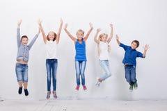 Grupp av lyckliga ungdomarsom hoppar på vit Arkivfoto