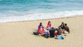 Grupp av lyckliga ungdomarsom sitter i en cirkel på den sandiga stranden arkivfoto