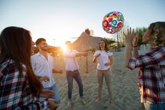 Grupp av lyckliga ungdomarsom spelar med bollen p? stranden arkivfoto