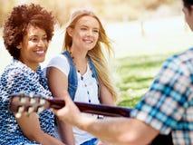 Grupp av lyckliga vänner med gitarren som har utomhus- gyckel Royaltyfria Foton