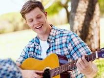 Grupp av lyckliga vänner med gitarren som har utomhus- gyckel Arkivbilder