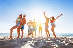 Grupp av lyckliga vänner på solnedgångstranden royaltyfri bild