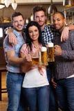 Grupp av lyckliga vänner som dricker öl på puben Arkivbilder
