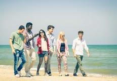 Grupp av lyckliga vänner som går på den blandras- stranden - Fotografering för Bildbyråer