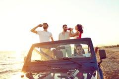 Grupp av lyckliga vänner som gör partiet i bil- ungdomarsom har gyckel som dricker champagne arkivbilder