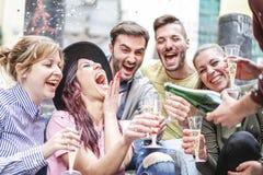 Grupp av lyckliga v?nner som g?r partiet som kastar konfettier och dricker utomhus- champagne - ungdomarsom har gyckel som firar  arkivbilder