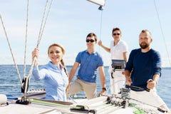 Grupp av lyckliga vänner som har ett parti på en yacht och dricker ch royaltyfri foto