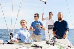 Grupp av lyckliga vänner som har ett parti på en yacht och dricker ch arkivbild