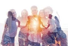 Grupp av lyckliga vänner som har gyckel på havstranden dubbel exponering arkivbilder