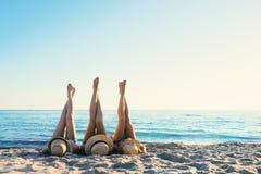 Grupp av lyckliga vänner som har gyckel på havstranden med ben upp Royaltyfria Bilder