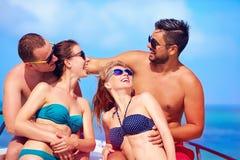 Grupp av lyckliga vänner som har gyckel på yachten, under sommarsemester Royaltyfri Bild