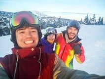 Grupp av lyckliga vänner som har gyckel Snowbarders och kamratskap för skidåkaregrupplag Arkivbild