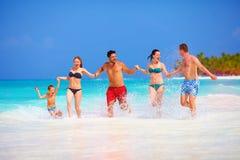Grupp av lyckliga vänner som har gyckel tillsammans på den tropiska stranden Fotografering för Bildbyråer