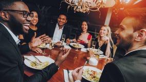 Grupp av lyckliga vänner som möter och har matställen royaltyfria bilder