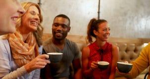 Grupp av lyckliga vänner som påverkar varandra, medan ha kaffe 4K 4k arkivfilmer