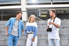 Grupp av lyckliga vänner som pratar i gatan stående två för pelikan för kamratskap för bakgrundsbegrepp våt mörk fotografering för bildbyråer