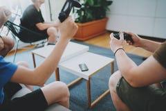Grupp av lyckliga vänner som sitter på en soffa i vardagsrum och spelar videospel Begrepp för avslappnande tid för familj hemmast Arkivfoto