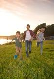 Grupp av lyckliga vänner som spelar lås-uppleken och spring i summ Royaltyfri Bild