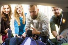 Grupp av lyckliga vänner som tar deras påsar från en bil för att starta en vandring Fotografering för Bildbyråer