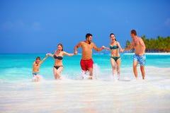 Grupp av lyckliga vänner som tillsammans kör på den tropiska stranden Arkivfoton
