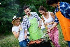 Grupp av lyckliga v?nner som ?ter och dricker ?l p? grillfestmatst?llen arkivbild