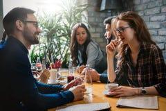 Grupp av lyckligt affärsfolk som äter i restaurang arkivfoton