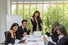 Grupp av lyckligt affärsfolk som i regeringsställning hurrar fira framgång Affärslaget firar ett bra jobb i kontoret asiat royaltyfria foton