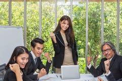 Grupp av lyckligt affärsfolk som i regeringsställning hurrar fira framgång Affärslaget firar ett bra jobb i kontoret asiat arkivfoto