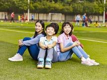 Grupp av lyckligt asiatiskt grundskola för barn mellan 5 och 11 årstudentsammanträde på gräs på Arkivfoto