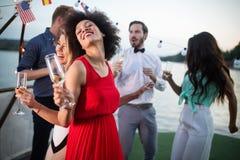 Grupp av lyckligt folk eller v?nner som har gyckel p? partiet arkivfoto