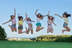 Grupp av lyckligt hoppa för tonår, royaltyfri foto