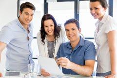 Grupp av lyckligt ungt affärsfolk i ett möte royaltyfri foto