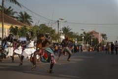 Grupp av män och kvinnor som bär traditionella kläder som utför under karnevalberömmarna i staden av Bisssau royaltyfri foto