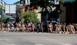 Grupp av män och kvinnor som marscherar med flaggor, i stadens centrum Denver, 2015 Royaltyfria Bilder