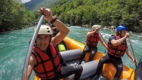 Grupp av män och kvinnor som Rafting på vitt vatten arkivbilder