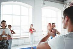 Grupp av män och kvinnor som värmer och gör konditionutbildning i grupp upp Det unga aktiva folket gör yoga tillsammans royaltyfria bilder