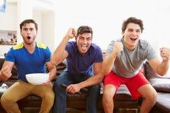 Grupp av män som sitter på Sofa Watching Sport Together royaltyfri fotografi