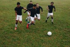 Grupp av män som spelar fotboll på fältet som kör för bollen Fotbollspelare som kör på fältet för besittning av bollen royaltyfri fotografi