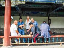 Grupp av män som spelar schack för traditionell kines i den långa corrien fotografering för bildbyråer