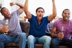 Grupp av män som tillsammans sitter på Sofa Watching TV Royaltyfri Bild