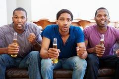 Grupp av män som tillsammans sitter på Sofa Watching TV Arkivfoto