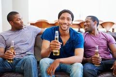 Grupp av män som tillsammans sitter på Sofa Watching TV Arkivbilder