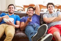 Grupp av män som tillsammans sitter på Sofa Watching TV Arkivfoton