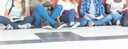 Grupp av mång- etniska tonåringar som placeras i hallet, talande e royaltyfri bild