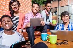 Grupp av mångfaldhögskolestudenter som lär på universitetsområde arkivbilder